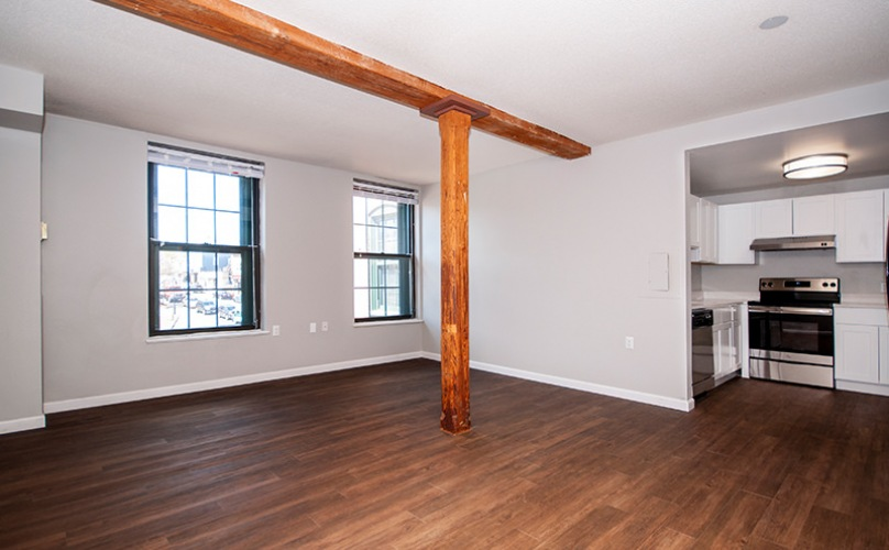 unfurnished living area with exposed wood beam
